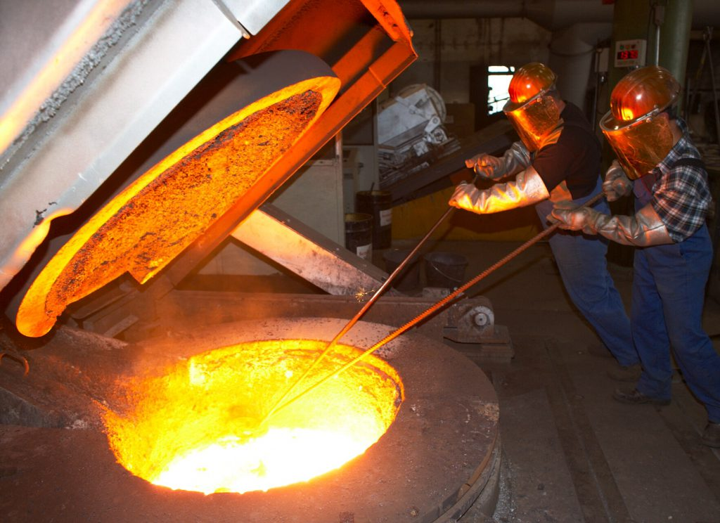 two steelworkers in a foundry with red hot furnace requiring industrial insulation