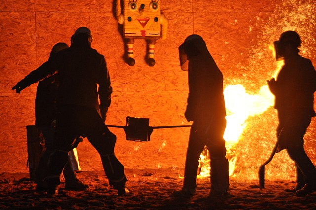 foundry workering in PPE carrying hot metal for blog by Emelin on furnace insulation basics