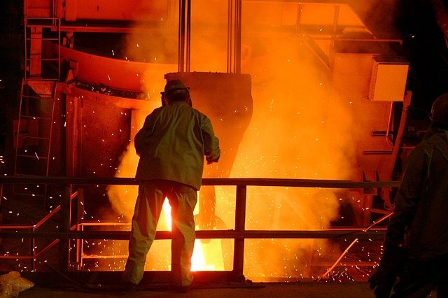 person in PPE leaning over vapours in foundry for blog by Emelin on furnace insulation basics
